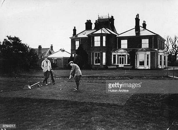 Golfers at the first tee at Bridlington golf course; the club house is in the background.