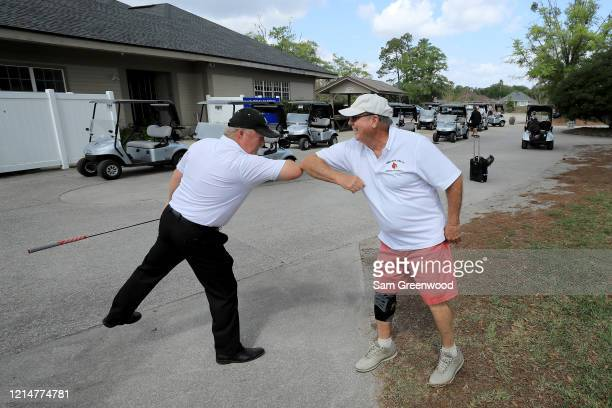 Golfers bump elbows at Windsor Parke Golf Club amid the Coronavirus outbreak on March 25 2020 in Jacksonville Beach Florida The World Health...