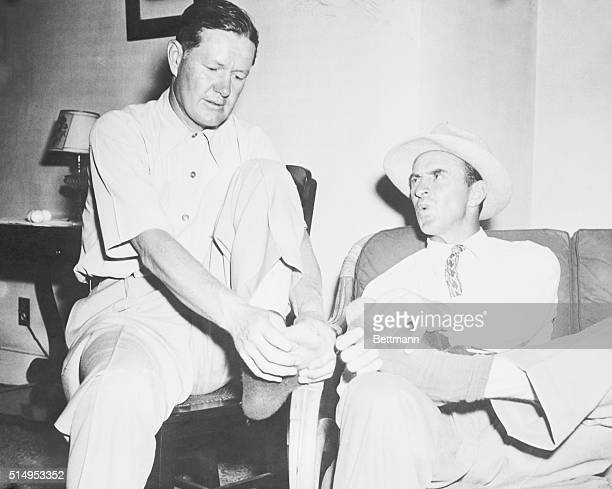 Golfers Byron Nelson and Sam Snead tied at 144 even par at the end of the first 36 holes of the 72 hole War Bond match ease their burning feet in...