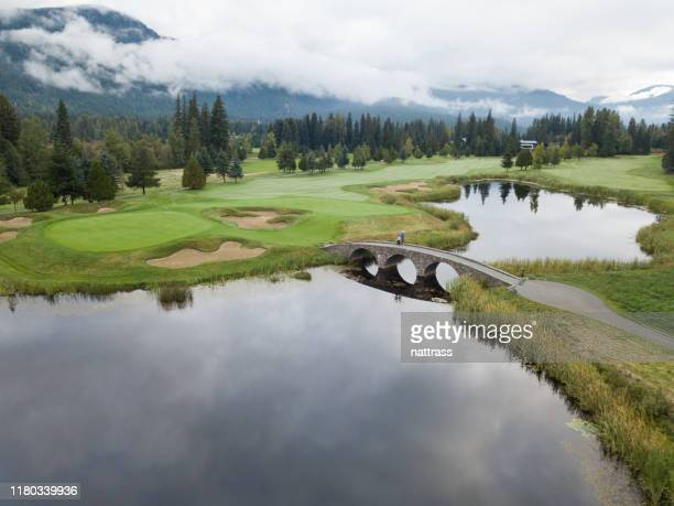 golfers cross the bridge towards the putting green - general view stock pictures, royalty-free photos & images