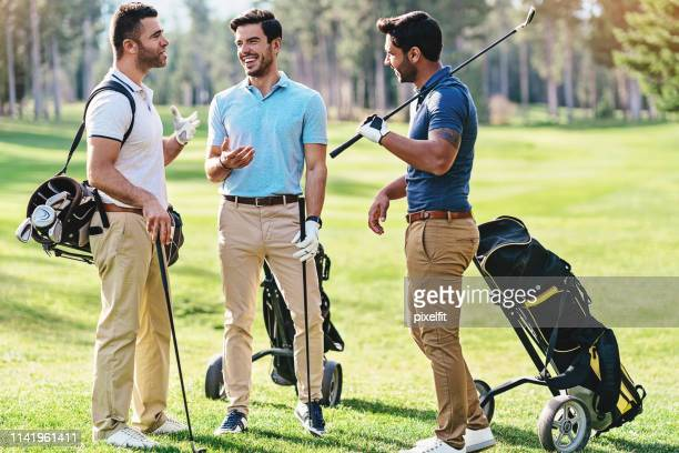 golfers enjoying the time together - khaki trousers stock pictures, royalty-free photos & images