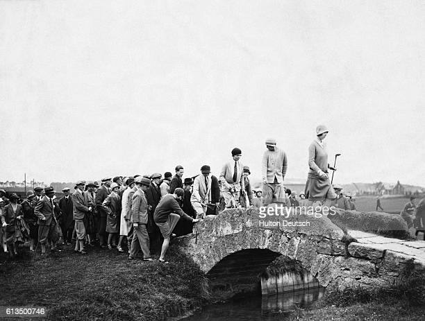 Golfers Glenna Collett Vare and Joyce Wethered lead spectators across a bridge at St Andrews during the 1929 Ladies British Open Golf Championship