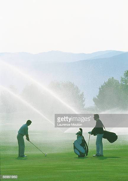 golfers golfing among sprinklers - amateur stock pictures, royalty-free photos & images
