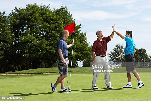 golfers high fiving on putting green standing next to golfer holding flag - golfer stock pictures, royalty-free photos & images