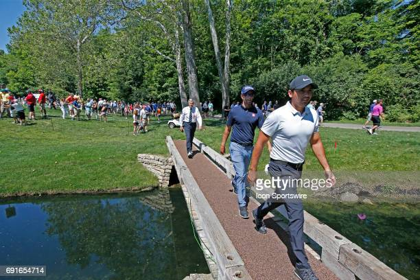 PGA golfers Jason Day and Adam Scott walk across a bridge after finishing on the first hole during the Memorial Tournament Second Round on June 02...