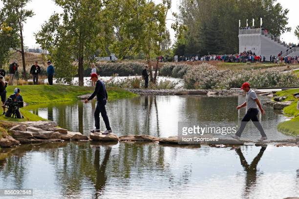 USA golfers Jordan Spieth and Patrick Reed walk across a stream by stepping on rocks as they walk to the 13th tee during the third round of the...