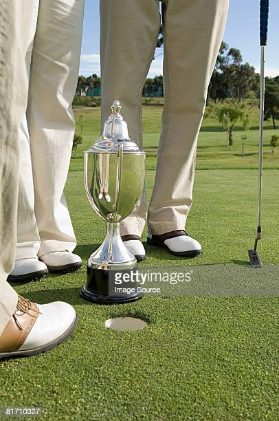 Golfers legs and a trophy