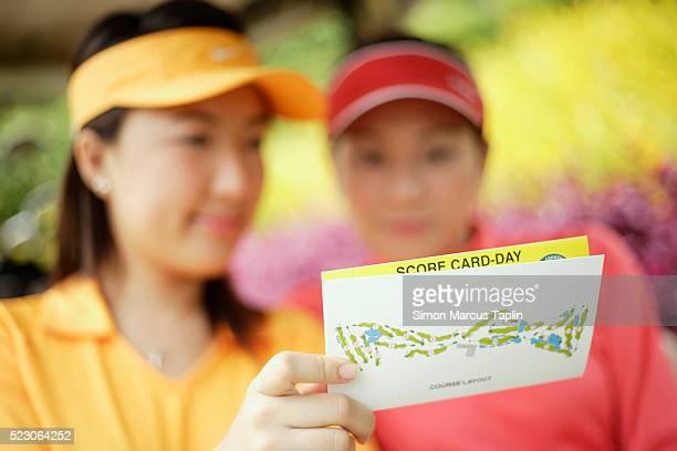 golfers looking at scorecard - 得点する ストックフォトと画像