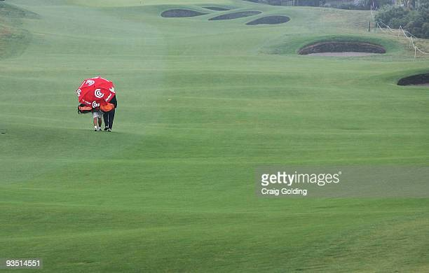 Golfers make their way back to the clubhouse after rain sets in during a practice round ahead of the Australian Open Golf Championship at New South...
