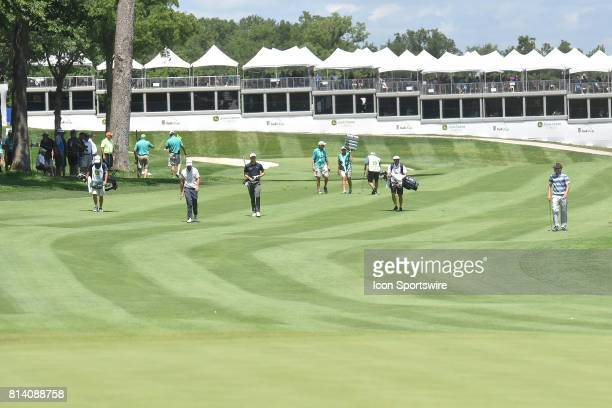 Golfers make their way down the fairway of the 18th hole during the first round of the John Deere Classic July 13 at TPC Deere Run Silvis IL