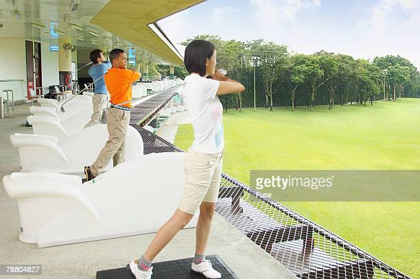 golfers on driving range - ゴルフ練習場 ストックフォトと画像