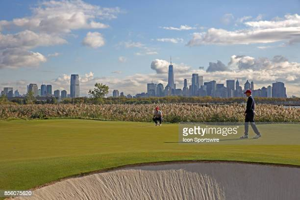 USA golfers Patrick Reed and Jordan Spieth putt on the 10th hole with the New York city skyline in the background during the third round of the...