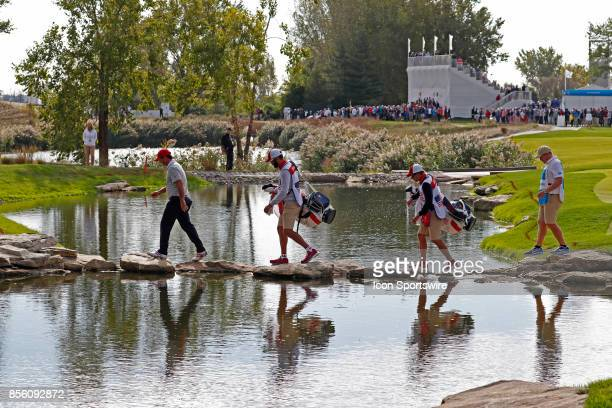 USA golfers Patrick Reed walks across a stream by stepping on rocks as he walks to the 13th tee during the third round of the Presidents Cup at...