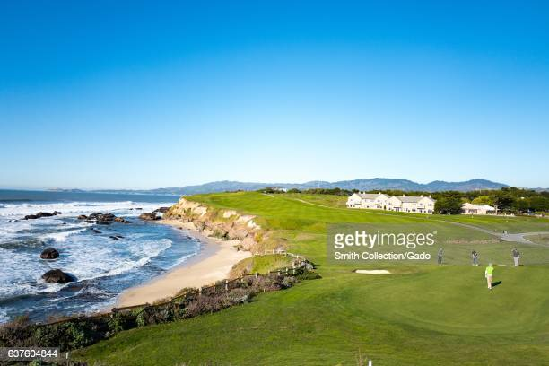 Golfers play on the Half Moon Bay Golf Links, with a portion of the Ritz Carlton Half Moon Bay hotel visible, in Half Moon Bay, California, December...