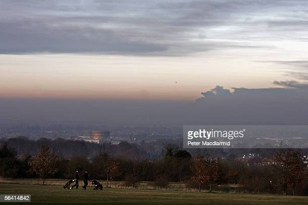 Golfers play on the North Downs as smoke rises from a fire at the Buncefield fuel depot in Hemel Hempstead on December 11 2005 seen from Epson Downs...