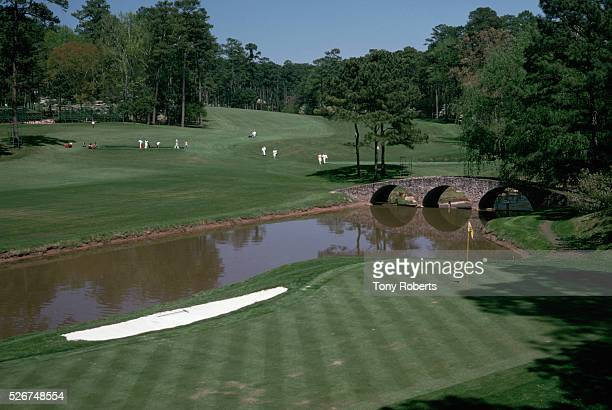 Golfers play the 12th hole at the Augusta National Course during the Masters Golf Tournament