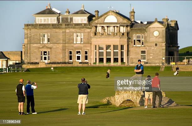 ST ANDREWS Golfers pose for photos on the Swilcan Bridge on the 18th hole of the Old Course in St Andrews Scotland on April 16 2011 Behind the bridge...