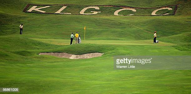Golfers putt out of the 10th green with the insignia of the Kuala Lumpur Golf and Country Club on display during the first round of the Maybank...