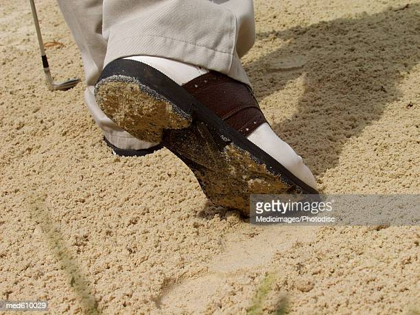 Golfer's shoe in sand trap, close-up