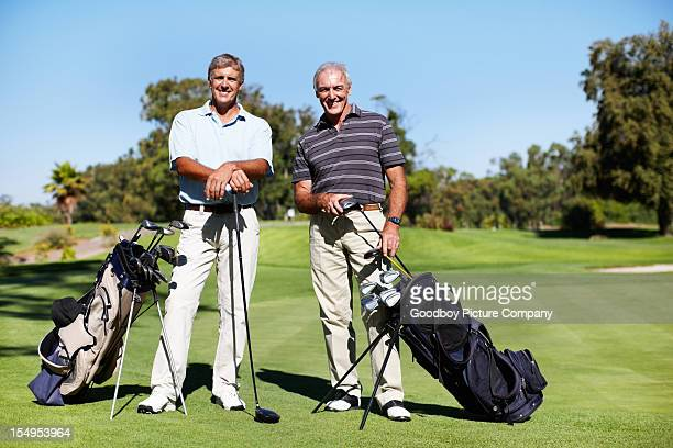Golfers standing with golf sticks on course