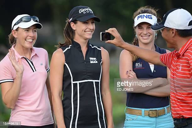 Golfers Stephanie Louden of the US Paige Mackenzie of the US and Liebelei Lawrence of the US pose for photos as they wait for a presentation ceremony...