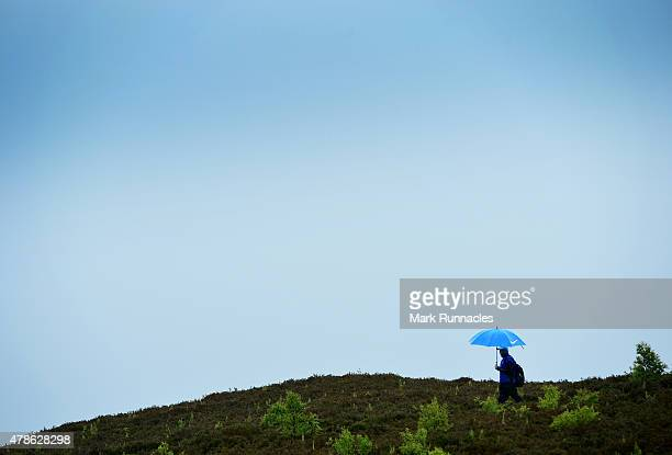 Golfers take cover under their umbrellas as rain starts to fall during the second round of the 2015 SSE Scottish Hydro Challenge at the MacDonald...