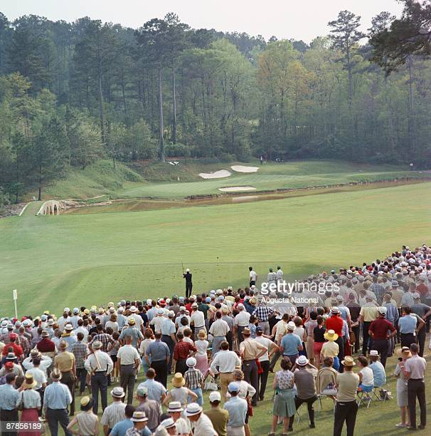 Golfers tee off on the 12th tee a part of Amen Corner before a large gallery during the 1965 Masters Tournament at Augusta National Golf Club in...
