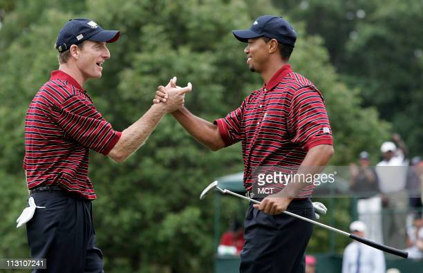Golfers Tiger Woods and Jim Furyk celebrate on the 18th green after their match against the International teams's Vijay Singh and Stuart Appleby at...