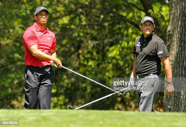 US golfers Tiger Woods and Phil Mickelson watch Woods' tee shot on the second hole during the final round of the US Masters at the Augusta National...