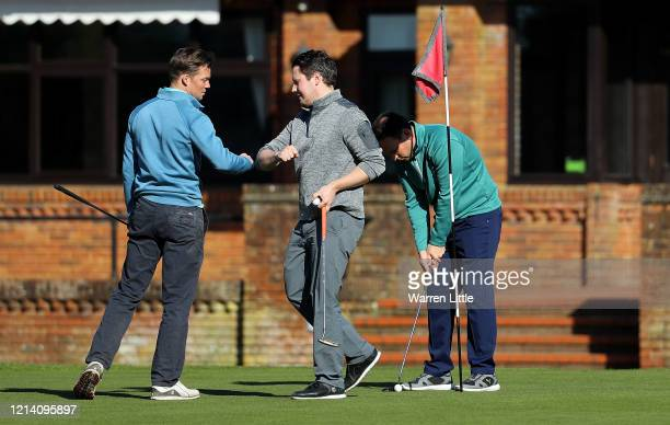 Golfers touch elbows instead of shaking hands as they play at Pine Ridge Golf Club on March 22, 2020 in Camberley, England. Coronavirus has spread to...