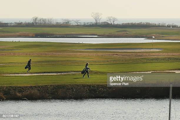 Golfers walk along the water during an afternoon of warm and sunny weather on December 13 2015 in Fairfield Connecticut Temperatures across much of...