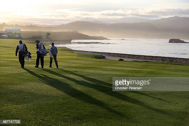 Golfers walk the 18th fairway during the continuation of the first round of the ATT Pebble Beach National ProAm at Pebble Beach Golf Links on...