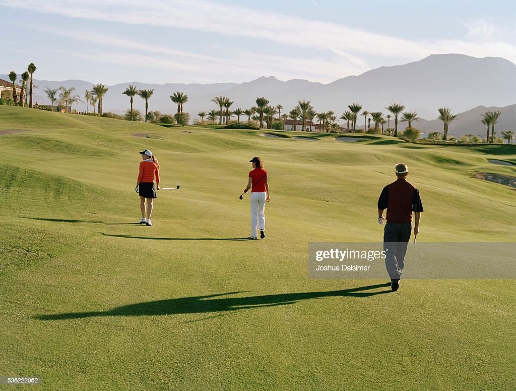 Golfers walking across golf course : Stock Photo