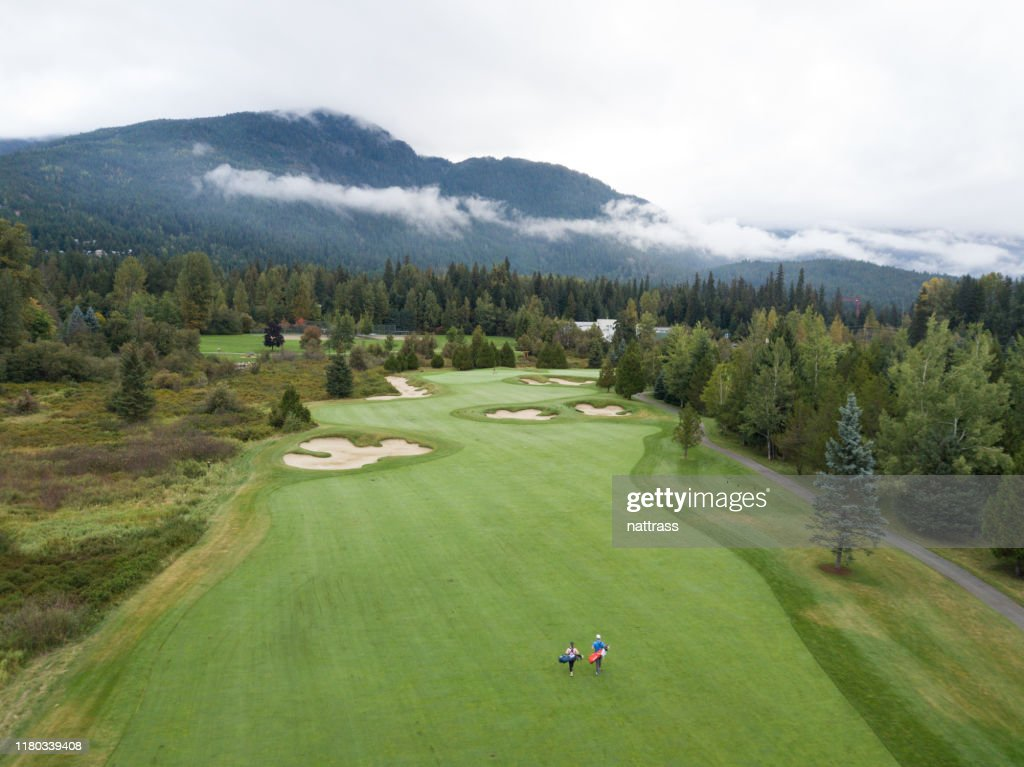 Golfers walking down the fairway : Stock Photo
