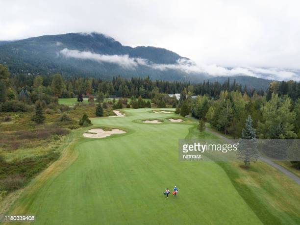 golfers walking down the fairway - golf course stock pictures, royalty-free photos & images