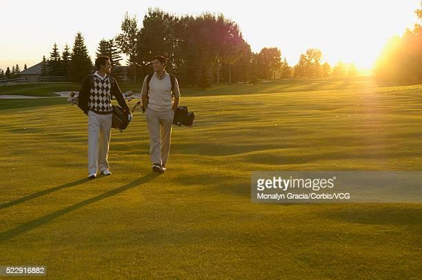 Golfers walking in evening sun