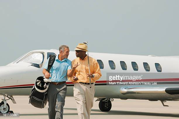 Golfers walking on airport tarmac