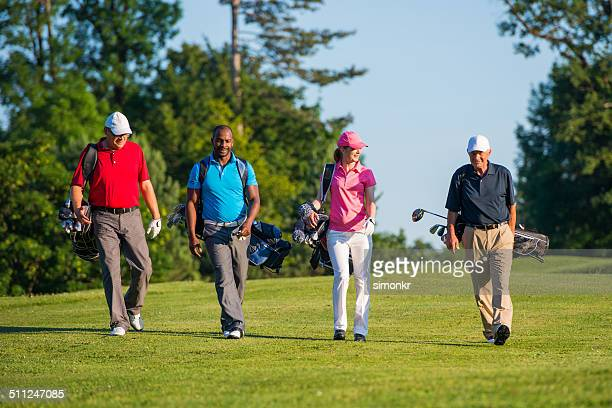 golfers walking on the golf course - four people stock pictures, royalty-free photos & images