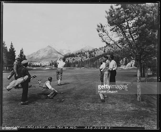 Golfers watch a companion tee off from hole 3 of the Banff Springs Golf Course
