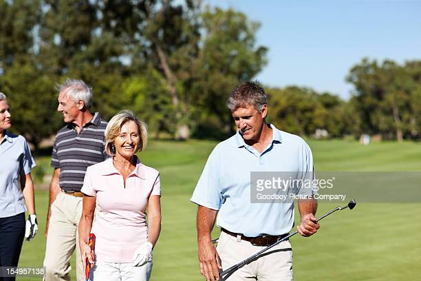 golfing couples chatting - green golf course stock pictures, royalty-free photos & images