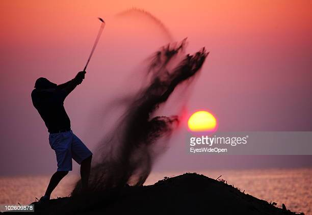 A golfplayer hits the ball out of a bunker on June 13 2010 in Rhodes Greece Rhodes is the largest of the Greek Dodecanes Islands