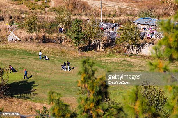 Golfplayers at The Royal Thimpu Golf Course beside of poor housings on November 18 2012 in Thimphu Bhutan