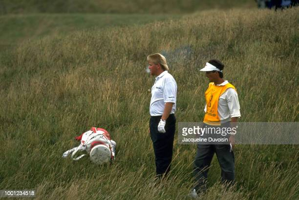 The British Open: John Daly with caddie standing in rough looking for ball while smoking a cigarette during Sunday play at Royal St. George's GC....