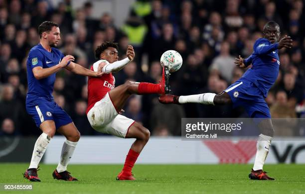 Golo Kante and Danny Drinkwater of Chelsea tackles Alex Iwobi of Arsenal during the Carabao Cup SemiFinal First Leg match between Chelsea and Arsenal...
