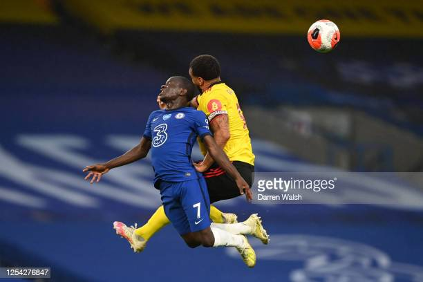 Golo Kante of Chelsea and Troy Deeney of Watford clash whilst jumping for the ball during the Premier League match between Chelsea FC and Watford FC...