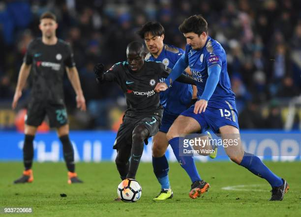 Golo Kante of Chelsea holds off Harry Maguire and Shinji Okazaki of Leicester City during The Emirates FA Cup Quarter Final match between Leicester...