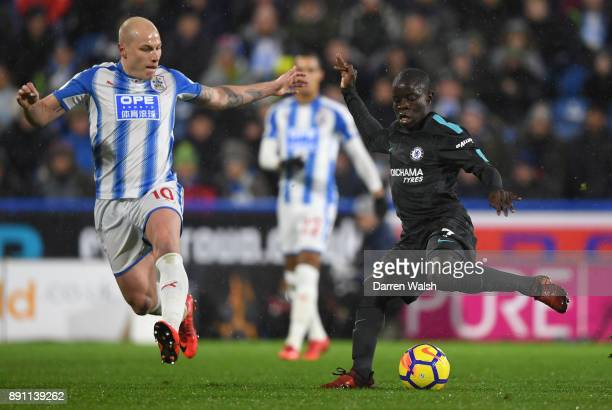 Golo Kante of Chelsea runs with the ball under pressure from Aaron Mooy of Huddersfield Town during the Premier League match between Huddersfield...