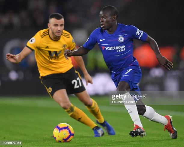 N'golo Kante of Chelsea runs with the ball under pressure from Romain Saiss of Wolverhampton Wanderers during the Premier League match between...