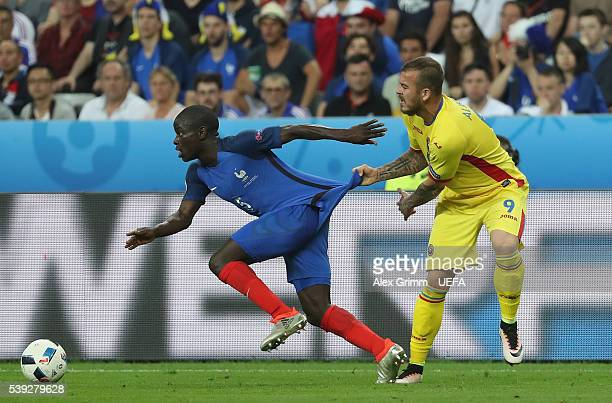 Golo Kante of France is pulled by Denis Alibec of Romania during the UEFA Euro 2016 Group A match between France and Romania at Stade de France on...