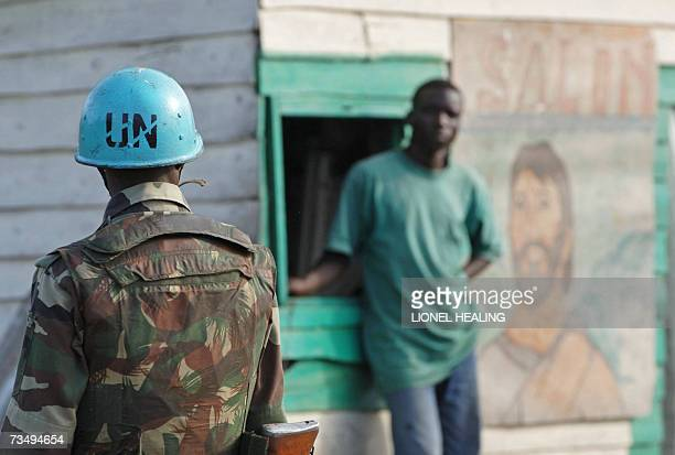 Goma, Democratic Republic of the Congo: A man watches a UN Indian peacekeeper standing guard, 05 March 2007, in Goma. An estimated three million...